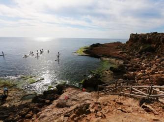 Cala de la Zorra - Cala de la Zorra - Escalinata de acceso a la plataforma rocosa. Grupo de personas practicando paddle surf.