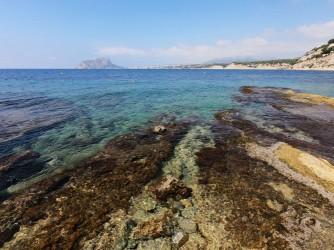 Cala Cap Blanc - Cala Cap Blanc - Zona rocosa con Peñón de Ifach al fondo, aguas cristalinas.