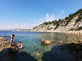 Cala Cap Blanc - Cala Cap Blanc - Personas accediendo al agua y practicando snorkel en un día con el mar en calma y aguas cristalinas.
