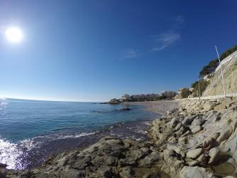 Cala Varadero - Cala Varadero - Zona rocosa de la cala vista des del nord. Passeig marítim a la dreta.