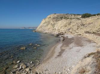 Playa Puntes del Moro - Playa Puntes del Moro - Zona sur de la playa con acantilado al fondo con detalle de las aguas cristalinas y del fondo marino rocoso.