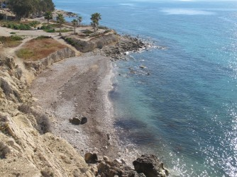 Playa Puntes del Moro - Playa Puntes del Moro - Zona sur de la playa vista desde el acantilado. Al fondo se observa la terraza con palmeras donde en verano se encuentra el chiringuito Sunset Puntes del Moro.