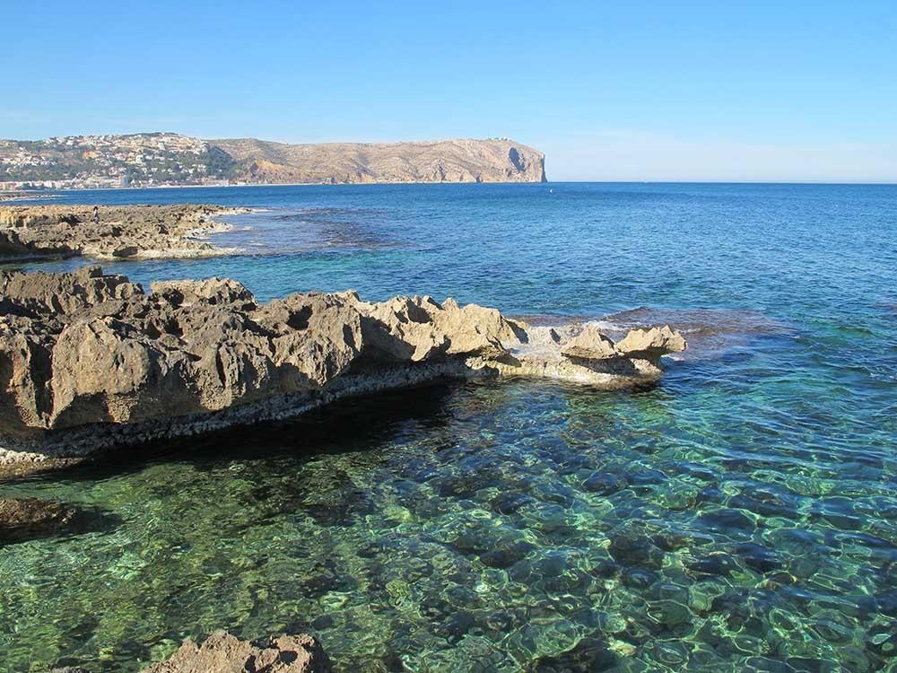 Cala del Ministro - Cala del Ministro - Zona rocosa con aguas cristalinas. Vistas del cabo de Sant Antoni al fondo.