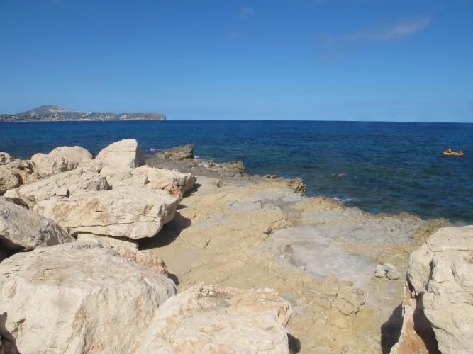 Cala del Penayl - Cala del Penayl - Zona de placa rocosa que forma la cala. Al fons vistesd del Cap d'Or.