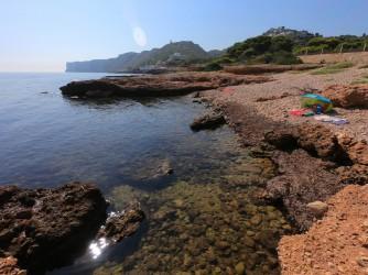 Cala Punta Negra - Cala Punta Negra - Otra cala de cantos rodados con restos de posidonia que nos indican la calidad de estas aguas. Cabo de San Antonio al fondo.
